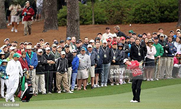 Rory McIlroy of Northern Ireland hits an approach shot on the second hole as a gallery of fans look on during the second round of the 2012 Masters...