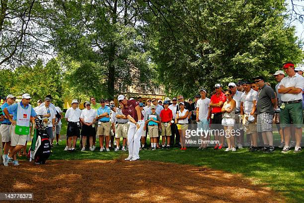 Rory McIlroy of Northern Ireland hits from the pine needles on the fourth hole as a gallery of fans look on during the first round of the Wells Fargo...