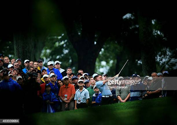 Rory McIlroy of Northern Ireland hits his second shot on the 12th hole as a gallery of patrons look on during the second round of the 96th PGA...