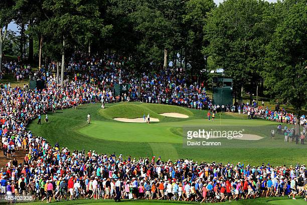 Rory McIlroy of Northern Ireland hits his second shot on the 14th hole as a gallery of patrons look on during the third round of the 96th PGA...