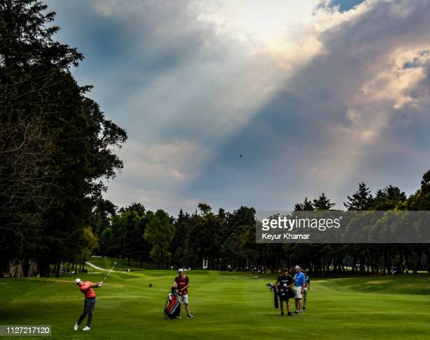 Rory McIlroy of Northern Ireland hits his second shot on the 14th hole fairway as sunbeams pass through the clouds during the final round of the...
