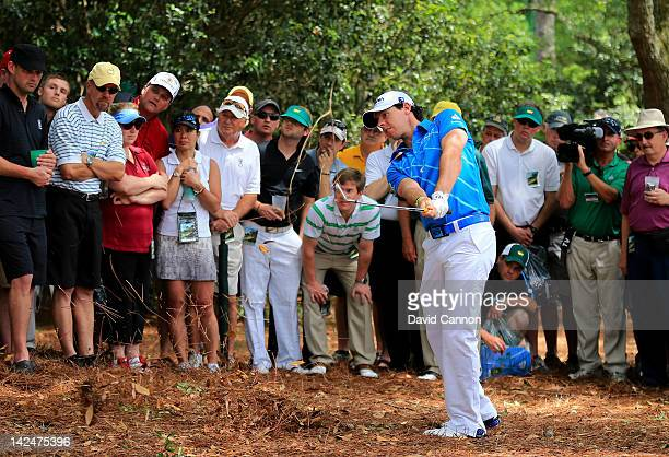 Rory McIlroy of Northern Ireland hits his second shot out of the rough on the first hole during the first round of the 2012 Masters Tournament at...