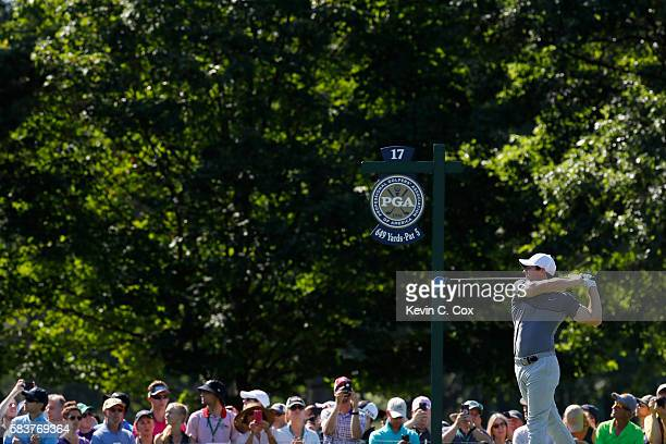 Rory McIlroy of Northern Ireland hits his tee shot on the 17th hole as fans look on during a practice round prior to the 2016 PGA Championship at...