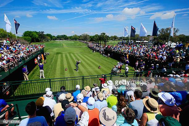 Rory McIlroy of Northern Ireland hits his tee shot on the first hole as a grandstand of fans look on during the third round of the Arnold Palmer...
