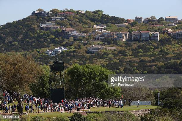 Rory McIlroy of Northern Ireland hits his tee shot on the second hole as Kevin Na of the United States and their caddies look on during the third...
