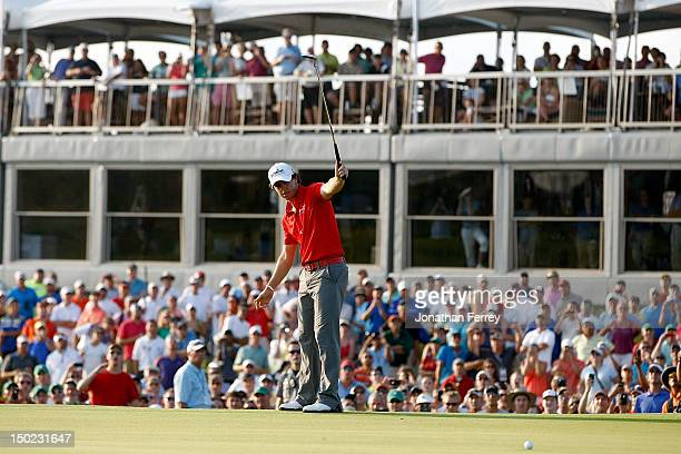Rory McIlroy of Northern Ireland holds his putter up in celebration as he putts on the 18th green during the Final Round of the 94th PGA Championship...