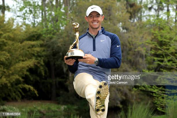 Rory McIlroy of Northern Ireland holds the new Players Championship trophy and shows off his 18 carat gold plated Nike golf shoes after his one shot...