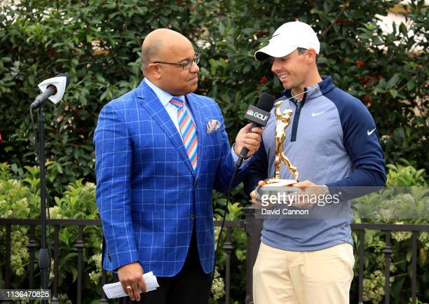 Rory McIlroy of Northern Ireland holds the new Players Championship trophy as he is interviewed by Mike Tirico after his one shot win as fans take...
