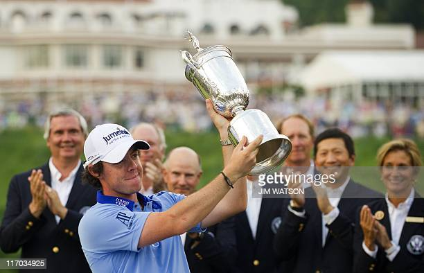 Rory McIlroy of Northern Ireland holds up the trophy after winning the 111th US Open by eight strokes over Jason Day with a record 268 at...
