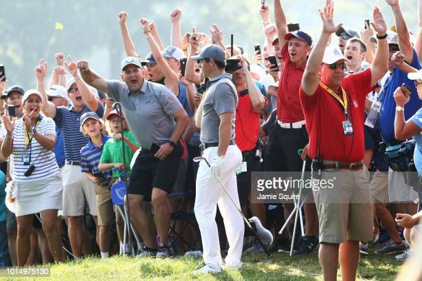 Rory McIlroy of Northern Ireland holes out on the 14th hole as fans cheer during the continuation of the weather delayed second round of the 2018 PGA...