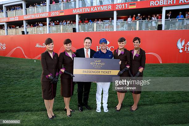 Rory McIlroy of Northern Ireland is presented with his prize from Etihad Airlines awarded to the player who scored most birdies in the tournament...