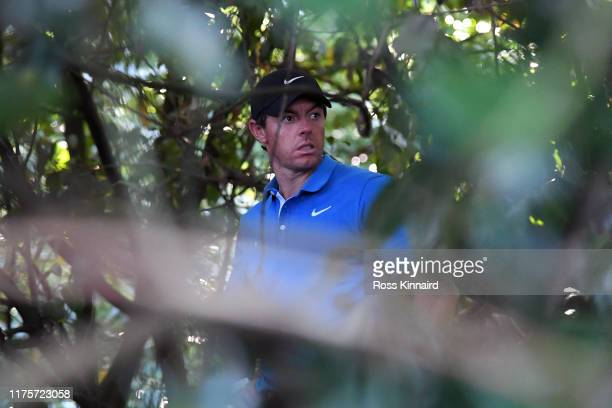 Rory McIlroy of Northern Ireland is seen within some trees on the 18th hole during Day One of the BMW PGA Championship at Wentworth Golf Club on...