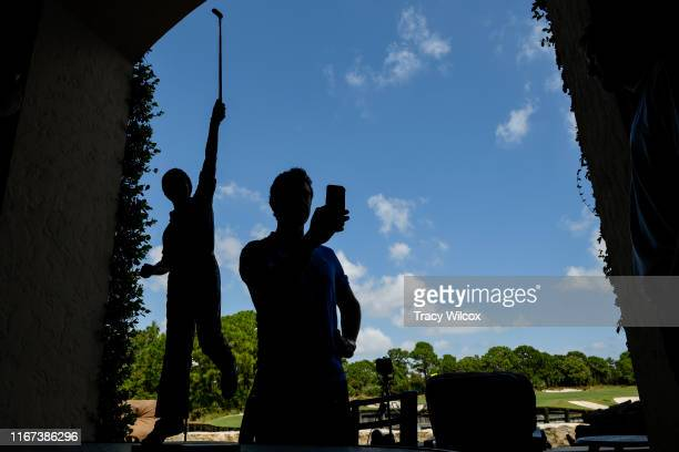 Rory McIlroy of Northern Ireland is silhouetted with the Player of the Year trophy as he takes a selfie during the Player of the Year ceremony at The...