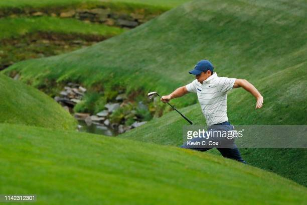 Rory McIlroy of Northern Ireland jumps across Rae's Creek on the 13th hole during the second round of the Masters at Augusta National Golf Club on...