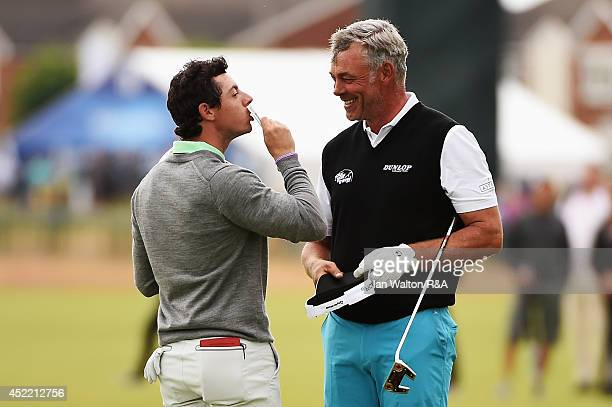 Rory McIlroy of Northern Ireland kisses money in celebration of winning a bet against Darren Clarke of Northern Ireland after their practice round...