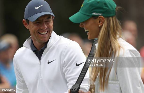 Rory McIlroy of Northern Ireland laughs with his wife Erica during the Par 3 Contest prior to the start of the 2018 Masters Tournament at Augusta...