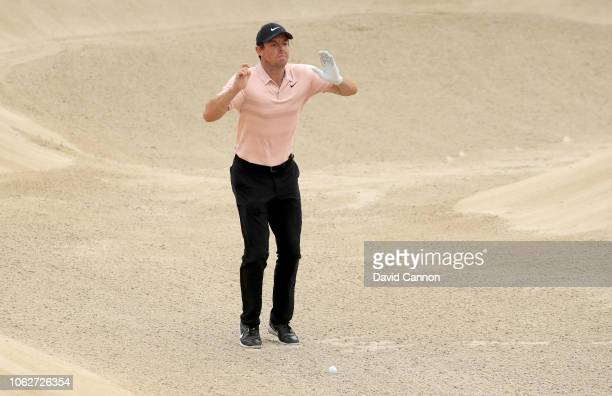 Rory McIlroy of Northern Ireland leaps top get a line for his second shot from a deep fairway bunker on the par 4 third hole during the third round...