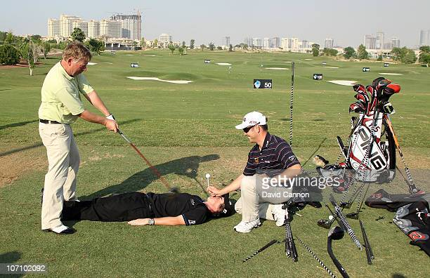 Rory McIlroy of Northern Ireland lies prone as Louis Oosthuizen of South Africa holds a very high tee on Rory's face as renowned trick shot artist...