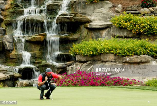 Rory McIlroy of Northern Ireland lines up his putt on the 13th green during the first round of the 96th PGA Championship at Valhalla Golf Club on...