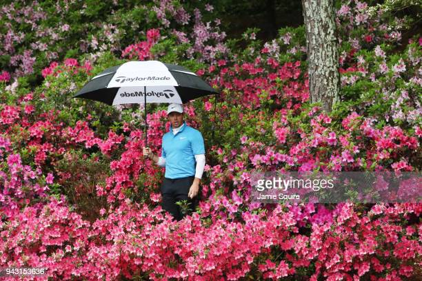 Rory McIlroy of Northern Ireland locates his ball in the flowers on the 13th hole during the third round of the 2018 Masters Tournament at Augusta...