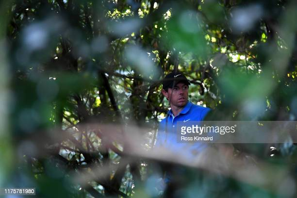 Rory McIlroy of Northern Ireland looking for his ball on the 18th hole during the first round of the BMW PGA Championship at Wentworth Golf Club on...