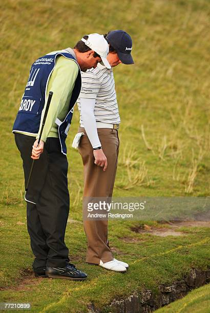 Rory McIlroy of Northern Ireland looks at his ball in the burn on the 18th hole during the third round of The Alfred Dunhill Links Championship at...