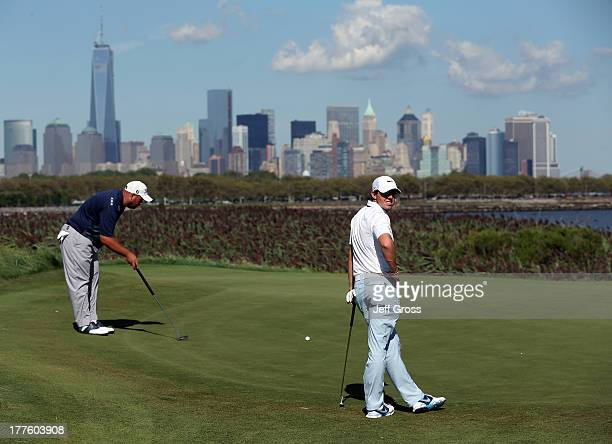 Rory McIlroy of Northern Ireland looks on while Brendon de Jonge of Zimbabwe lines up a putt during the third round of The Barclays at Liberty...