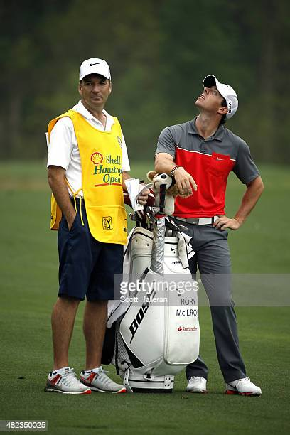 Rory McIlroy of Northern Ireland looks up with his caddy JP Fitzgerald on the second hole during round one of the Shell Houston Open at the Golf Club...