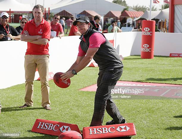 Rory McIlroy of Northern Ireland passes a rugby ball in the spectator village as Welsh rugby legend Jonathan Davies looks on during the first round...
