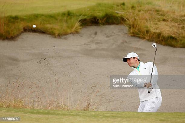 Rory McIlroy of Northern Ireland plays a bunker shot on the 13th hole during the first round of the 115th US Open Championship at Chambers Bay on...