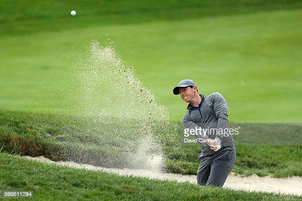 Rory McIlroy of Northern Ireland plays a shot from a bunker on the seventh hole during the final round of the Deutsche Bank Championship at TPC...