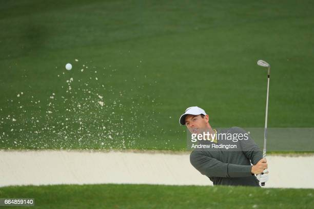 Rory McIlroy of Northern Ireland plays a shot from a bunker on the 18th hole during a practice round prior to the start of the 2017 Masters...