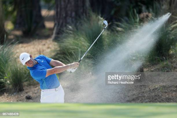 Rory McIlroy of Northern Ireland plays a shot from a bunker on the tenth hole during the second round of THE PLAYERS Championship on the Stadium...