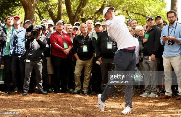 Rory McIlroy of Northern Ireland plays a shot from the pine straw on the first hole as a gallery of patrons look on during the final round of the...