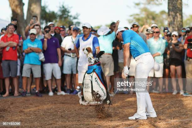 Rory McIlroy of Northern Ireland plays a shot from the pine straw on the 18th hole during the second round of THE PLAYERS Championship on the Stadium...