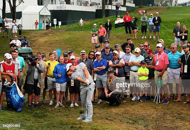 Rory McIlroy of Northern Ireland plays a shot from the rough on the 18th hole during the continuation of the weather delayed first round of the US...