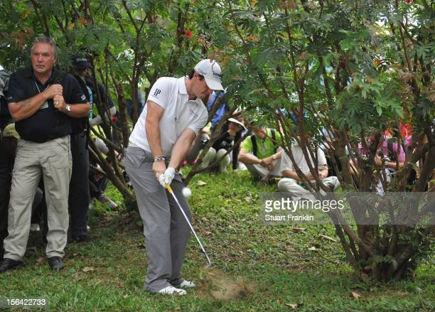 Rory McIlroy of Northern Ireland plays a shot left handed from a bush on the sixth hole during the first round of the UBS Hong Kong open at The Hong...