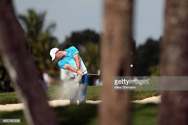 Rory McIlroy of Northern Ireland plays a shot out of the bunker on the seventeenth hole during the first round of the World Golf...