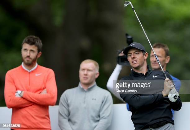 Rory McIlroy of Northern Ireland plays a shot watched by Manchester United legends Michael Carrick Paul Scholes and Teddy Sheringham during the proam...