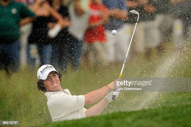 Rory McIlroy of Northern Ireland plays from a bunker during the second day of previews to the 109th US Open on the Black Course at Bethpage State...