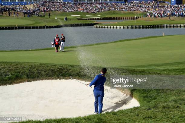 Rory McIlroy of Northern Ireland plays his second shot on the 18th hole from an appaling lie off the tee in his match against Justin Thomas during...