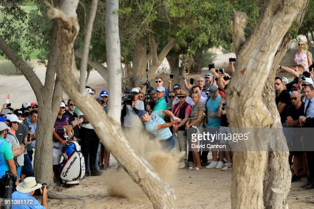Rory McIlroy of Northern Ireland plays his second shot on the par 4 16th hole from the trees during the final round of the Omega Dubai Desert Classic...