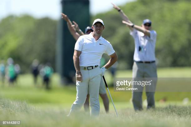 Rory McIlroy of Northern Ireland plays his second shot on the third hole as two marshals signal the ball has gone right during the first round of the...