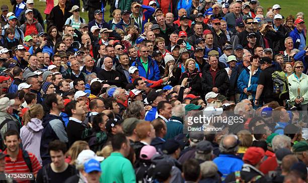 Rory McIlroy of Northern Ireland plays his second shot to green at the par 4 1st hole from amongst a huge gallery during the first round of the 2012...