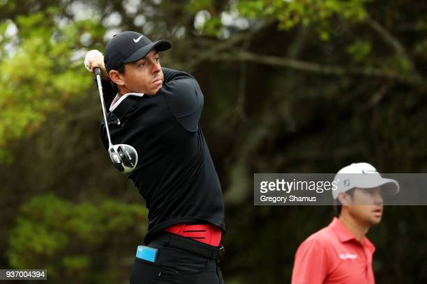 Rory McIlroy of Northern Ireland plays his shot from the fifth tee as Brian Harman of the United States looks on during the third round of the World...