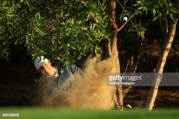 Rory McIlroy of Northern Ireland plays his third shot from a bunker on the tenth hole during round one of the Abu Dhabi HSBC Golf Championship at Abu...