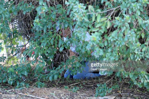 Rory McIlroy of Northern Ireland plays his third shot on teh par 4, sixth hole by crawling into the bush and playing off his knees during the third...