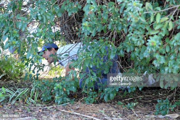 Rory McIlroy of Northern Ireland plays his third shot on teh par 4 sixth hole by crawling into the bush and playing off his knees during the third...
