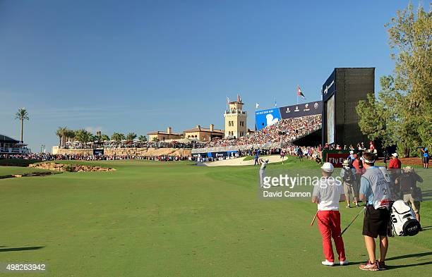 Rory McIlroy of Northern Ireland plays his third shot on the par 5 18th hole as his playing partner Andy Sullivan of England looks on during the...