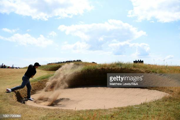 Rory McIlroy of Northern Ireland plays out a bunker on the 1st fairway during round one of the 147th Open Championship at Carnoustie Golf Club on...